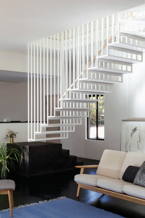 The two storeys of Hideaway House are linked by a finely crafted steel staircase composed of slender steel rods and floating timber treads.