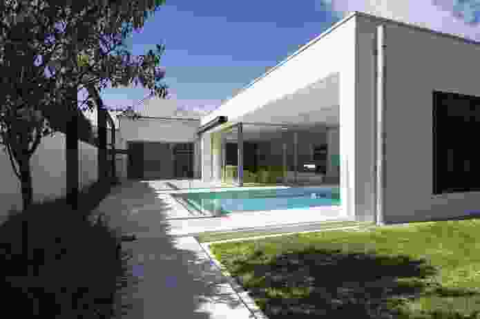 The white, rectilinear addition to the rear seamlessly abuts the existing house.