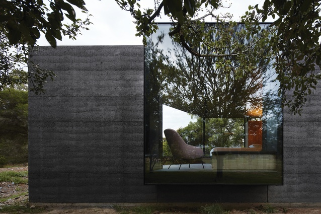 A large window box, extruding from the rammed-earth wall, frames views of the fruit trees and stables beyond.