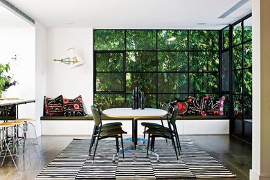 A window seat stretches along the northern edge of the dining room, with a multi-paned window framing a wall of greenery outside.
