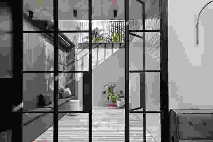 A sunken courtyard, lined with pale green tiles, captures northern light, making the rumpus room bright and inviting.