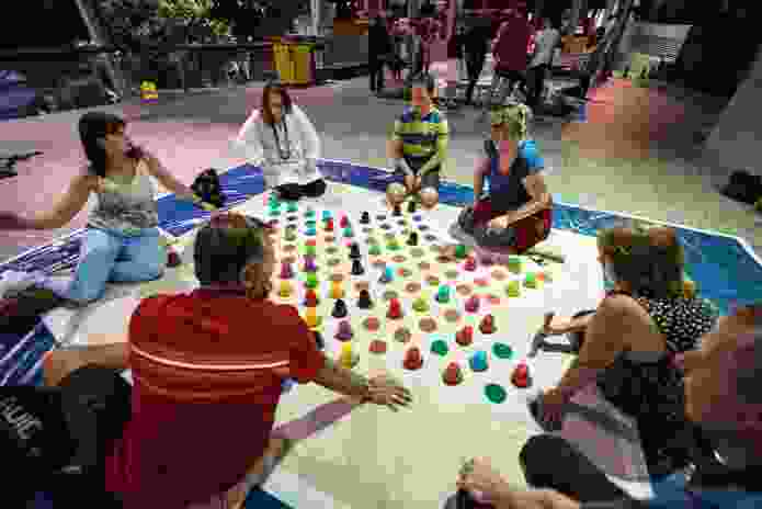 A giant game of chinese checkers gets underway. A giant mahjong game can be seen in the background.