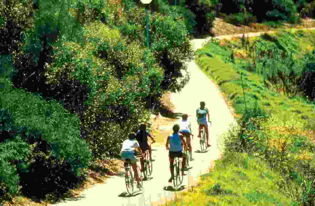 Cyclists wind along the river's edge on the park's shared path, circa 1980s.