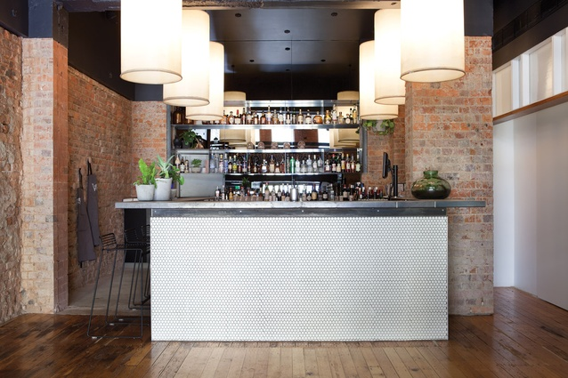 White tiles to the bar front contrast with rough, exposed brick.