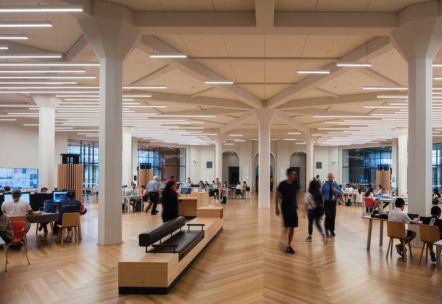 Quad的条形照明穿过天花板上原有的钢筋混凝土条,突出了旧的结构。