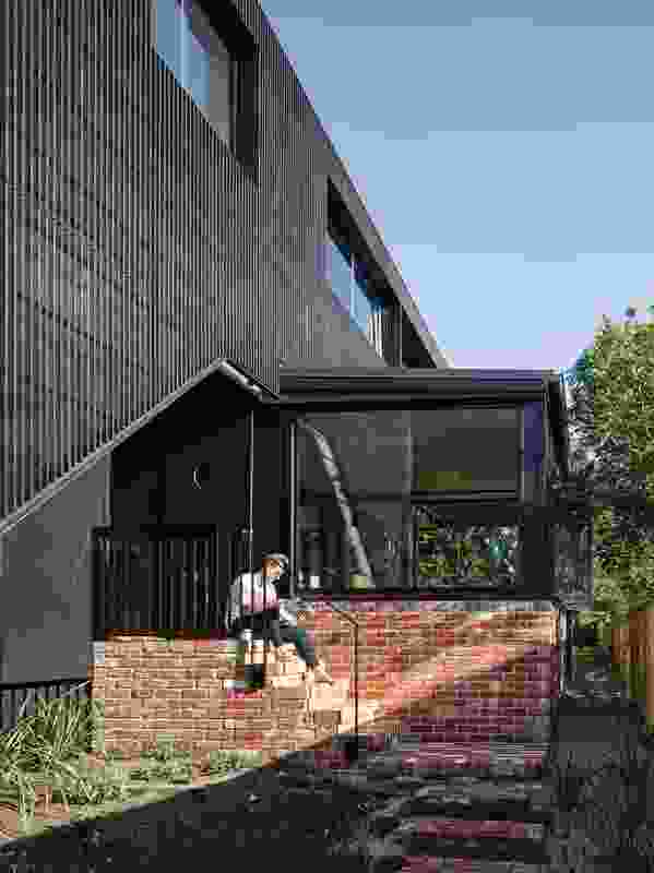The cantilevered living area, which offers access to the garden from both ends, is wrapped in red brick.
