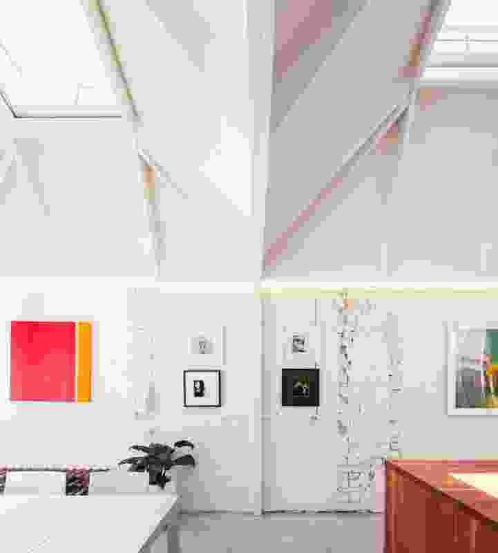 The double-height ceiling lends the house a feeling of spaciousness. Artwork: Lou Rendina (bottom left, bottom right and top right of four set, and far left painting); artist unknown (top left of four set); Samantha Everton (far right).