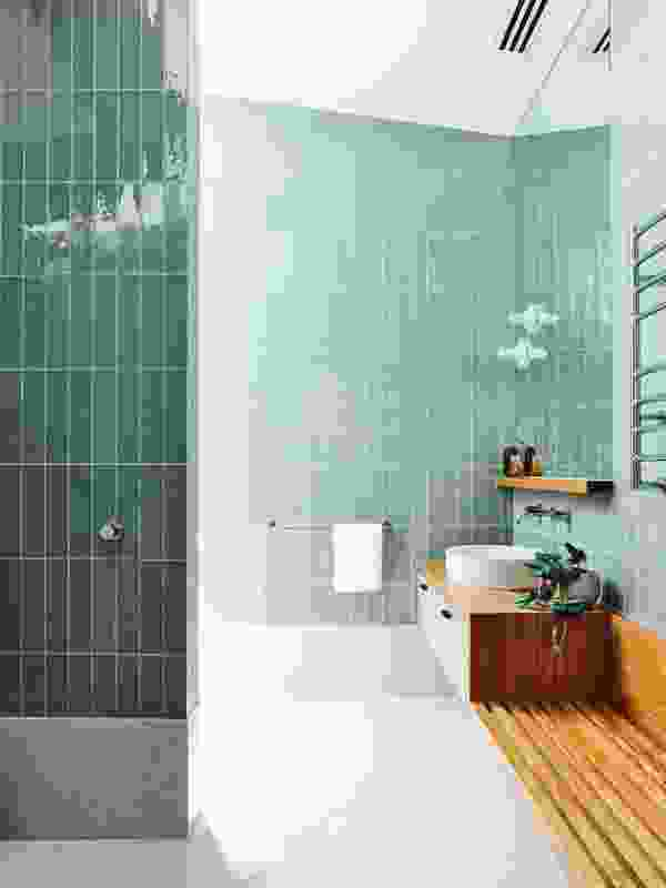 The upper-level ensuite is tiled in an inviting green that references the home's easy connection with nature.