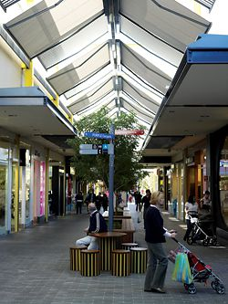 Retractable fabric roofing along main pedestrian loop provides weather protection.