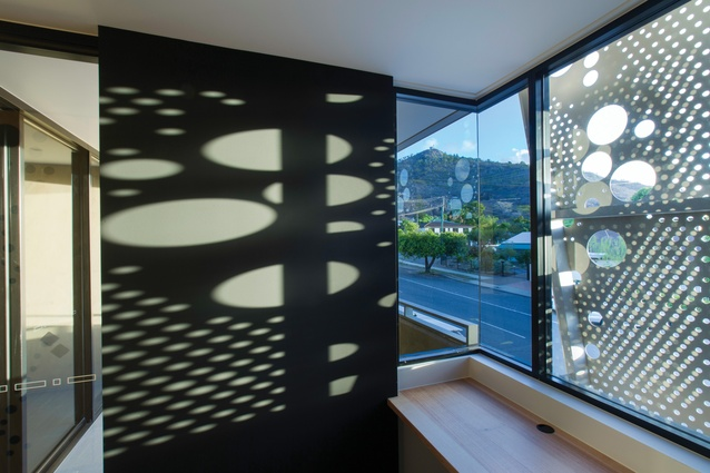 Laser-cut metal screens provide climate control while also casting bubble patterns on the interior surfaces.