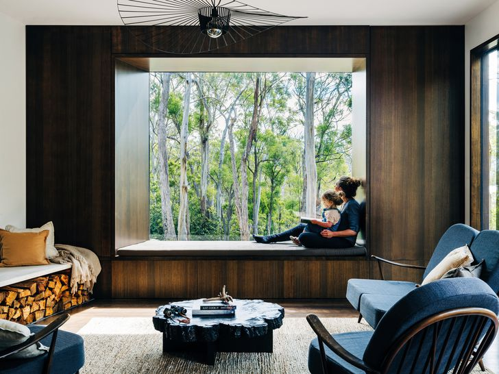 A large window in the living space frames the vista of surrounding bushland.