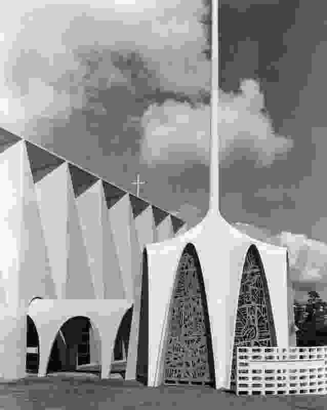 The octagonal baptistery chapel, featuring eight tilted hyperbolic paraboloid arches and a all, slender spire.
