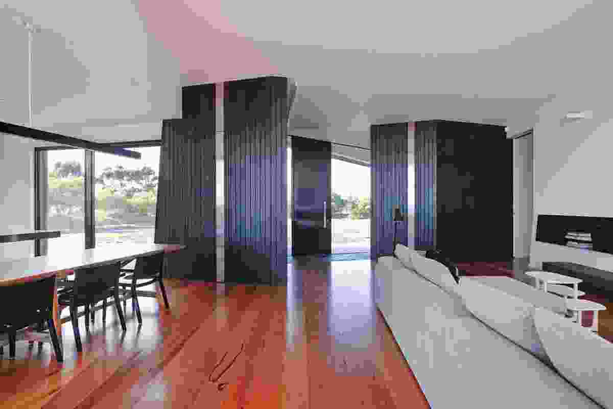 The living area is made from a collision of two forms, delineating the lounge, dining and kitchen.