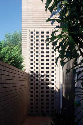 The pixelation of the entry tower allows shafts of light to penetrate the brick screen, creating a memorable arrival point.