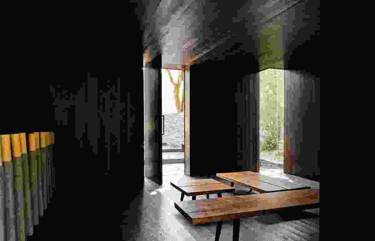 The enveloping interior of the meditation room is clad in dark wood on ceiling, walls and floor. Light pours in through a corner window, revealing a tranquil pool.