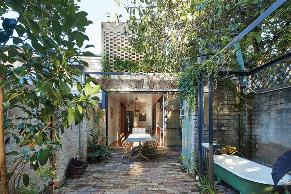 The original outhouse acts as a threshold point between the outdoor dining and bathing areas.