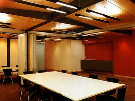 The flexible spaces of the meeting rooms, with the red wall beyond.