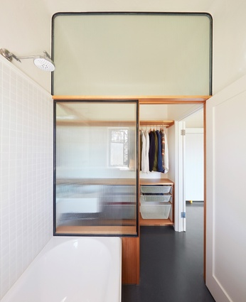 The shower screen has been expanded to become an entire glazed wall, demarcating space and providing privacy.