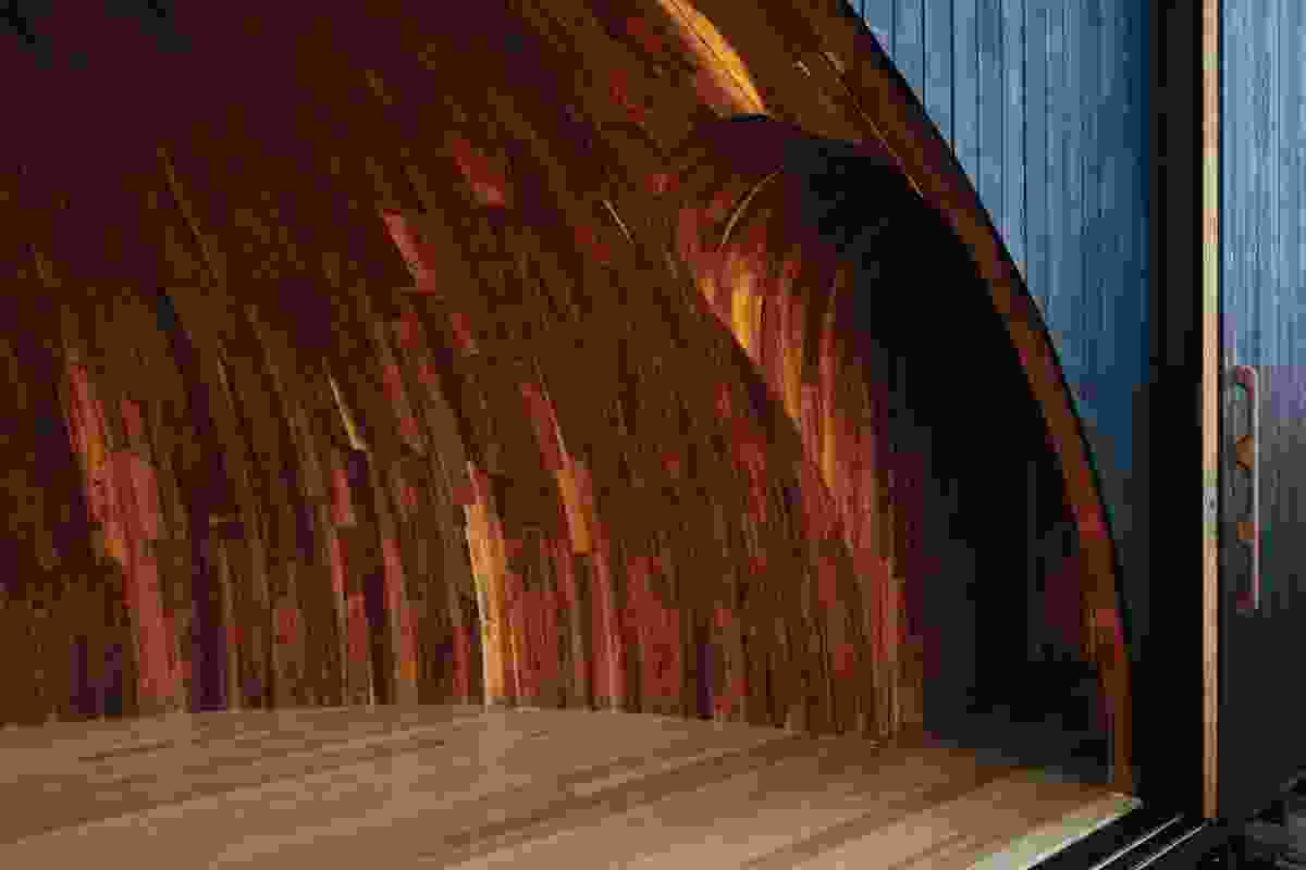 The bark cladding of traditional north-eastern Tasmanian Aboriginal shelters is reimagined in the half-dome of the camp's central pavilion as a red-stained timber lining reminiscent of tree sap or an open wound.