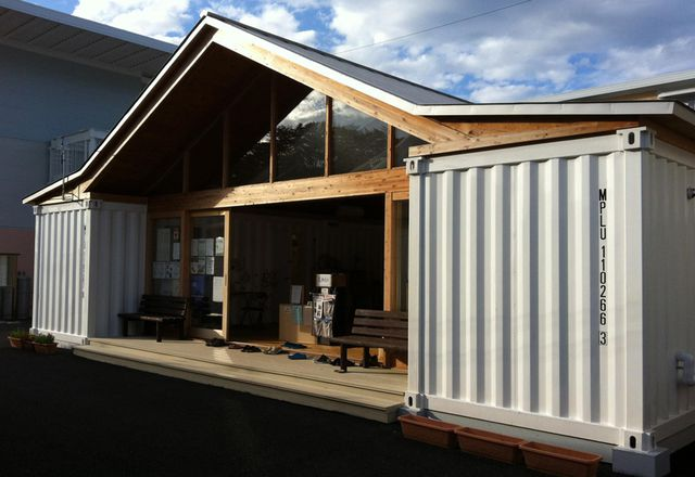 Ban's community center is a large pitch-roofed space with amenities tucked into shipping containers.
