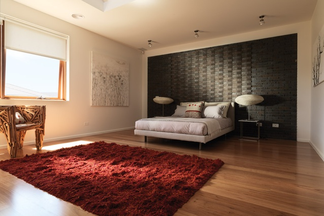 The main bedroom on the second level features a painted panel of recycled bricks, similar to the living room.
