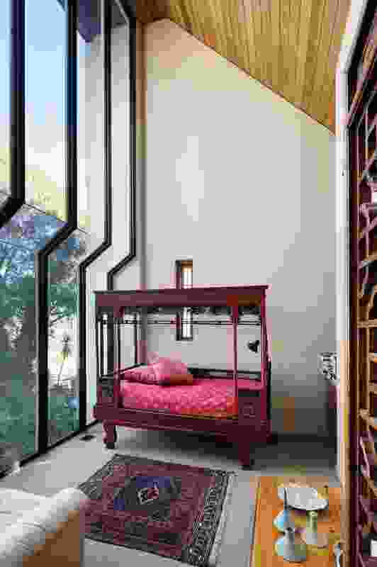 A small study/guestroom has a soaring, two-storey, stepped-glass wall to the valley view.