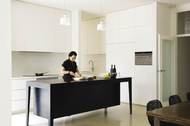 A black, metal-framed island bench, topped with Portoro marble is featured among a series of seamless, white built-in cupboards.