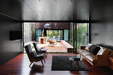 Black melamine lines the interior of the living spaces, which have a strong connection to the outdoor courtyards.