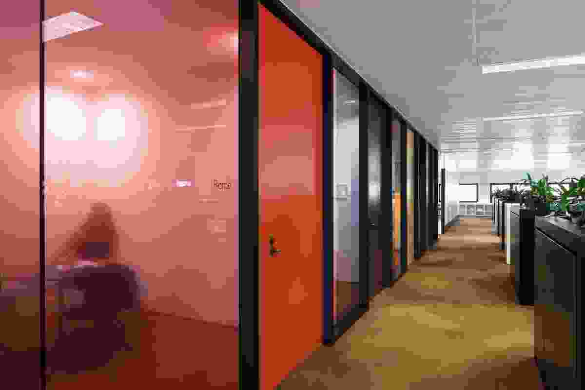 Meeting rooms are framed in coloured glass, recalling offices of the 1970s.