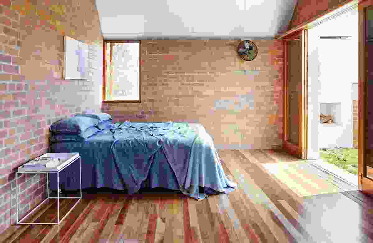 Expressed brick walls continue into the bedrooms, softened by the warmth of the spotted gum floorboards. Artwork: Cornelia Burless.