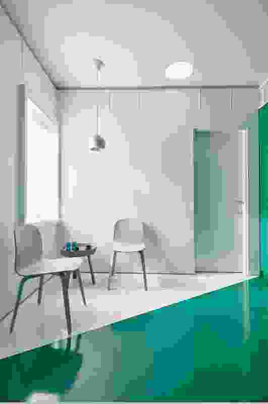 A diagonal line is struck across the kitchen floor to articulate a bold, emerald-toned preparation area and a white sitting corner.