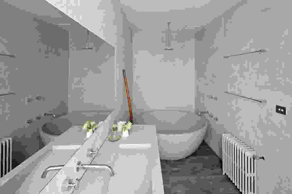 The main feature of the grey-toned bathroom is  a terracotta bath tub.