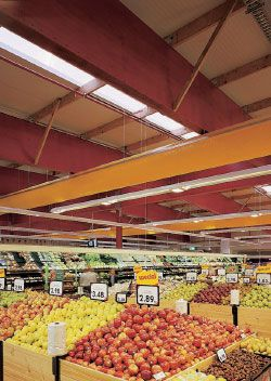 Interior views. Strip skylights, integrated with the roofing system, bathe the supermarket sales floor in daylight.