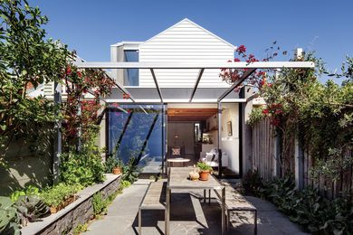 Custom steel-framed sliding doors open onto a small but sunny courtyard.