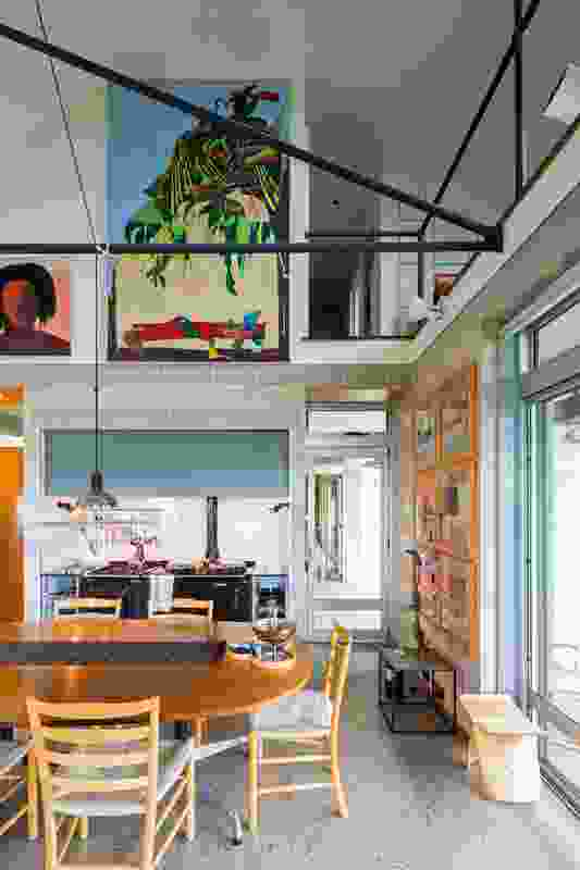 The upper-level volume is pushed to the side to accommodate a void down to the kitchen and dining below. Artwork: Roland Shlick (main).