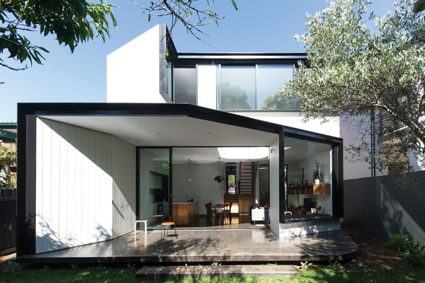 The rear elevation's strong angles are defined by thick, black steel window reveals that contrast against the white plywood cladding.
