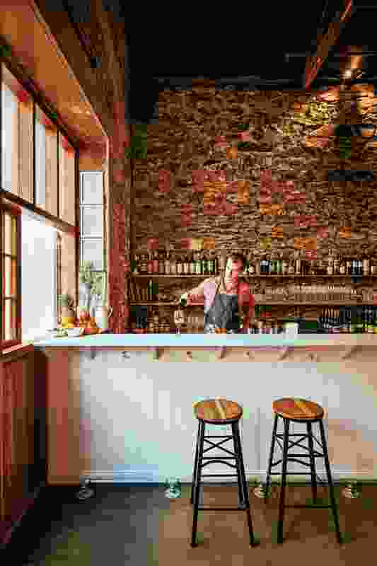 Bluestone walls found during site demolition form the bar's backdrop.