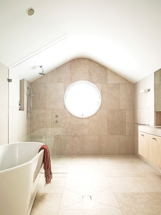 The curves seen in the exterior of the extension are carried though into the shape of the ceiling in the kids' bathroom.