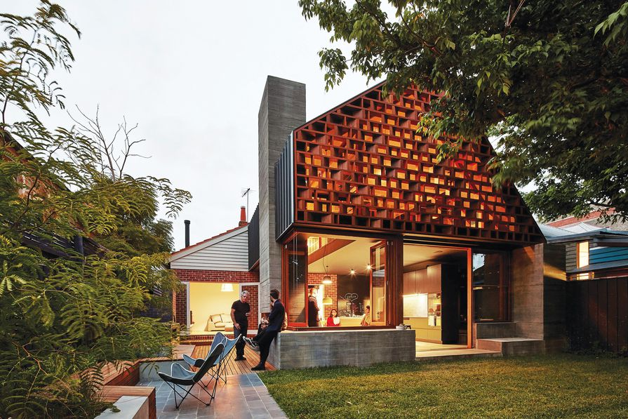 A large-scale timber screen gives a rhythm of pattern, texture and shadows to the rear facade of the extension.