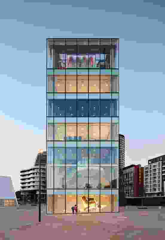 A six-storey tower contains a series of community facilities, including a music room, tech lab and reading room. At the plaza level, visitors can peer down into the library below.