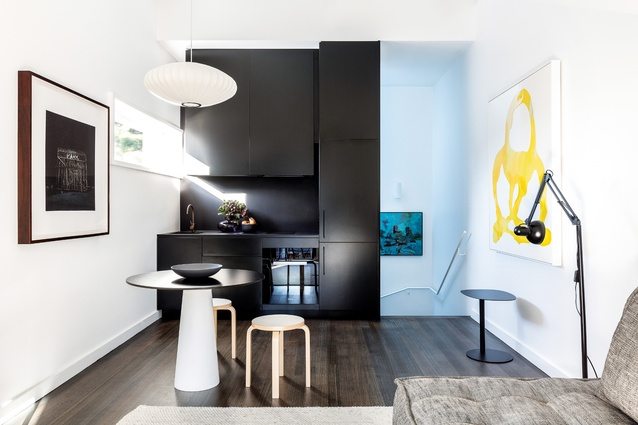The self-contained apartment is served by a small but functional kitchen and living space on the top floor. Artwork: Unknown (left); Henry Mullholland (at stair); Tamara Mendels (right).