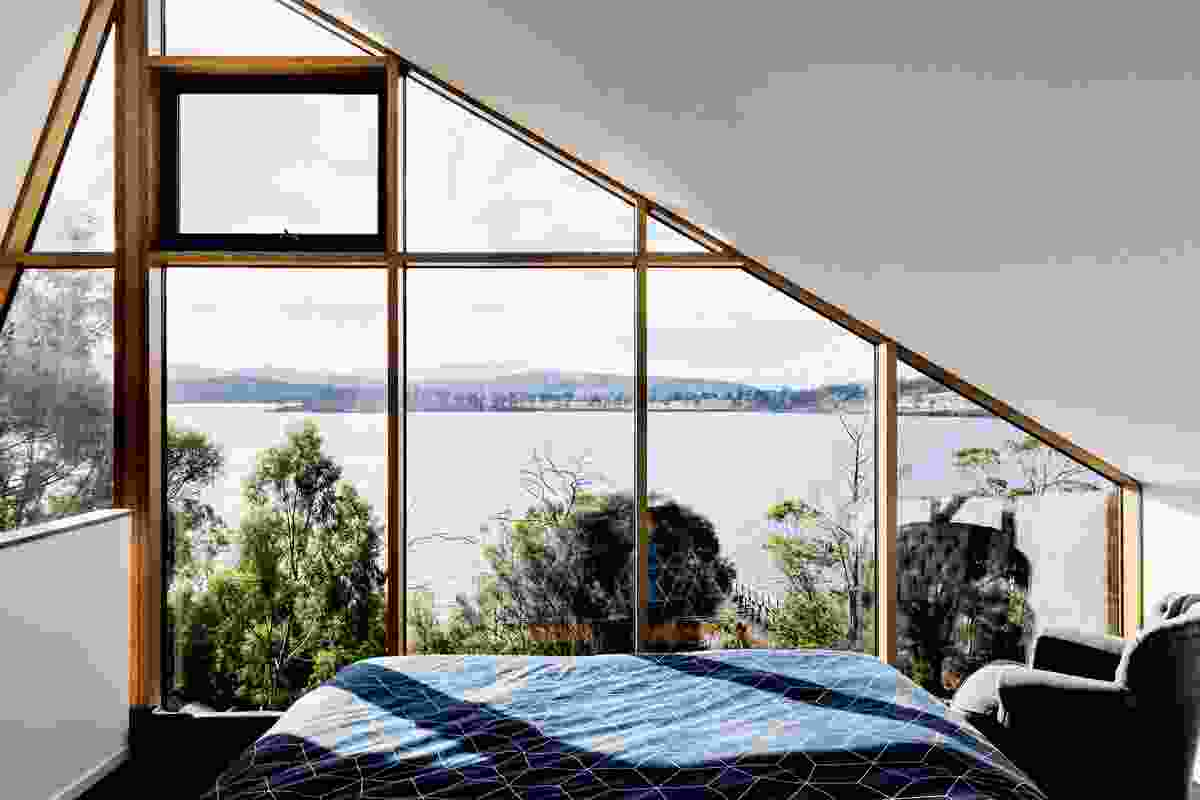 Perched above the living area, the main bedroom captures river views.