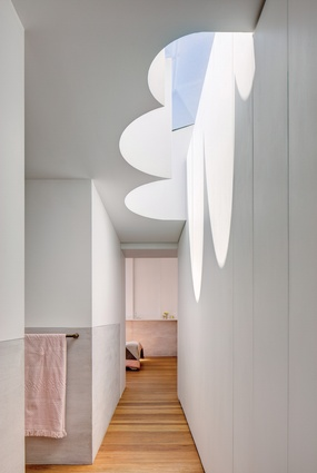 """A dramatic """"cloud light,"""" referencing the form of the original hallway arch, appears to float at the top of the stairs."""