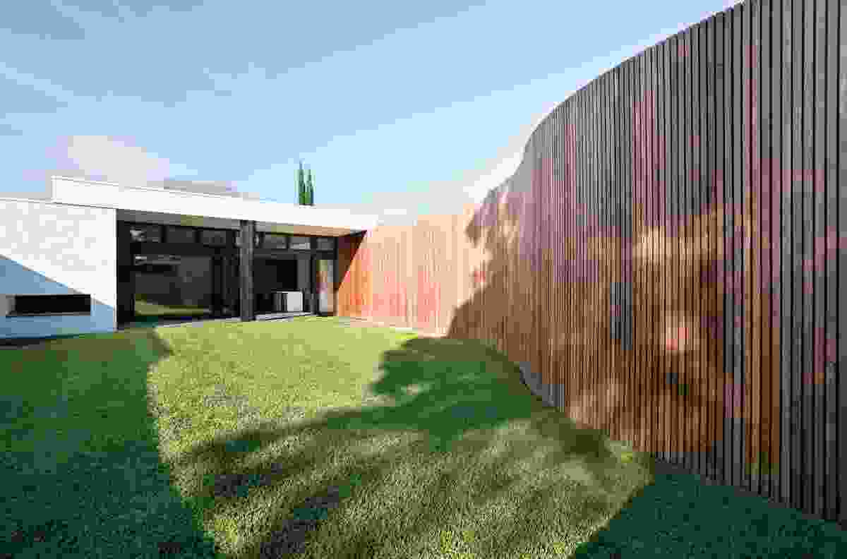 A curving wall of timber battens caresses the lawn. It conceals a garage, workshop and service yard.