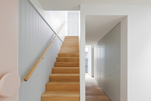 The laundry is concealed behind grooved timber joinery that defines the walls of the living space.
