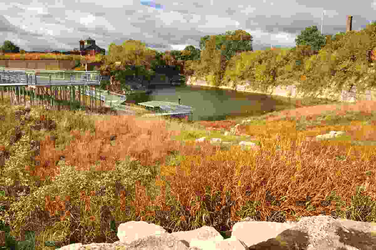 At Henry Palmisano Park, a steel walkway leads into the sloping site, offering views of the exposed quarry cliff face.