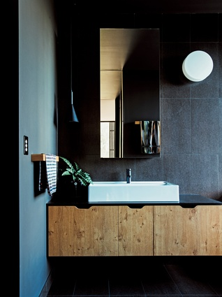 The bathroom boasts a dark, sophisticated palette, offset by the warmth of solid American oak joinery.