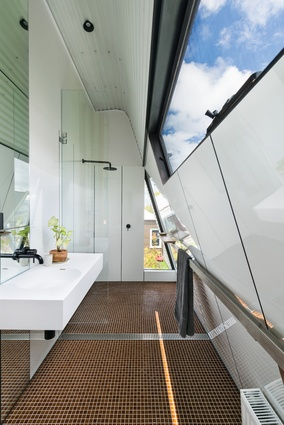 A clerestory window floods the bathroom with light, while a small triangular window offers glimpses of the garden.