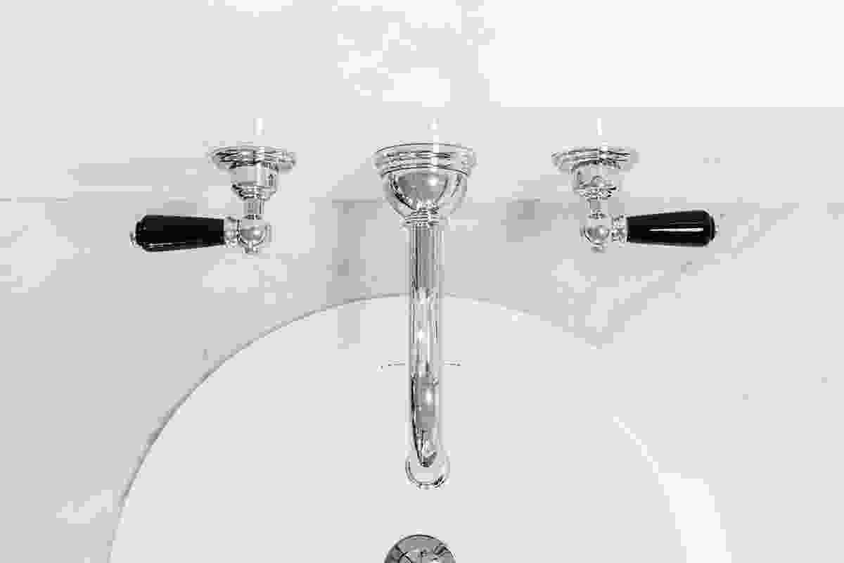 Wall-mounted basin set with country spout and black porcelain levers.