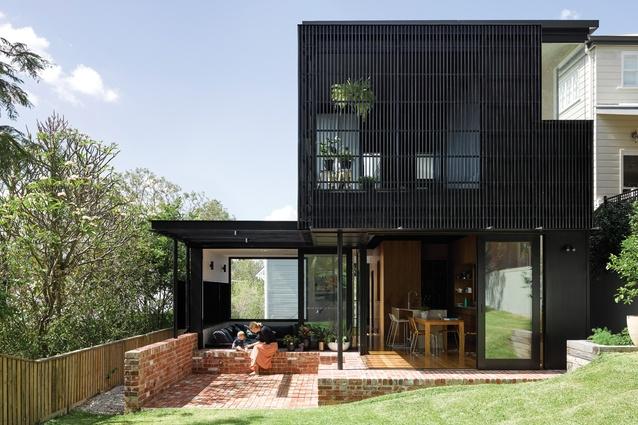 The sunken living room ends in a brick-floored courtyard beside the back garden.